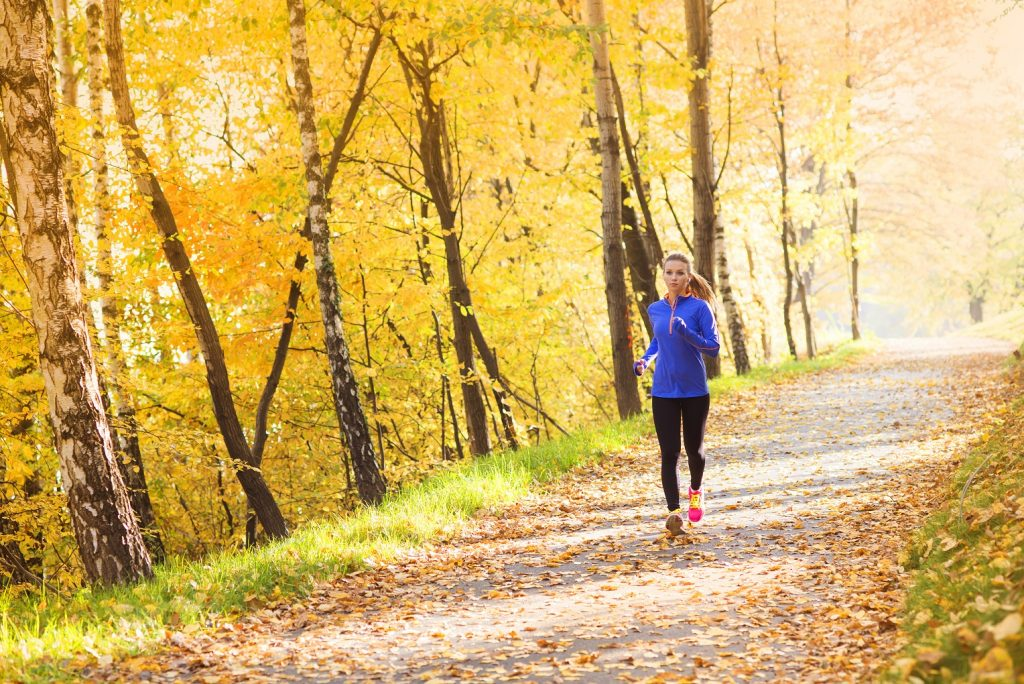 real estate in Kelowna Sean Skuter woman running on trail surrounded by yellow leaves
