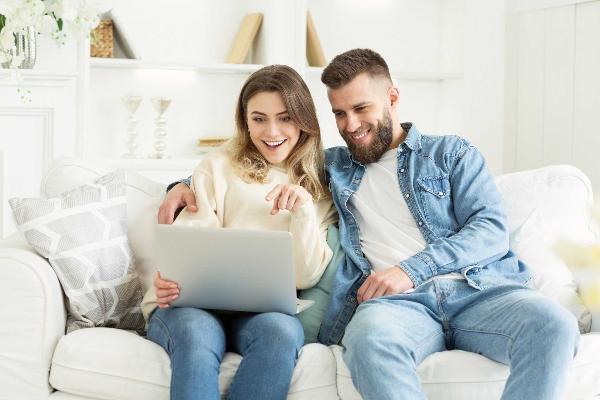 Couple buying new home from laptop