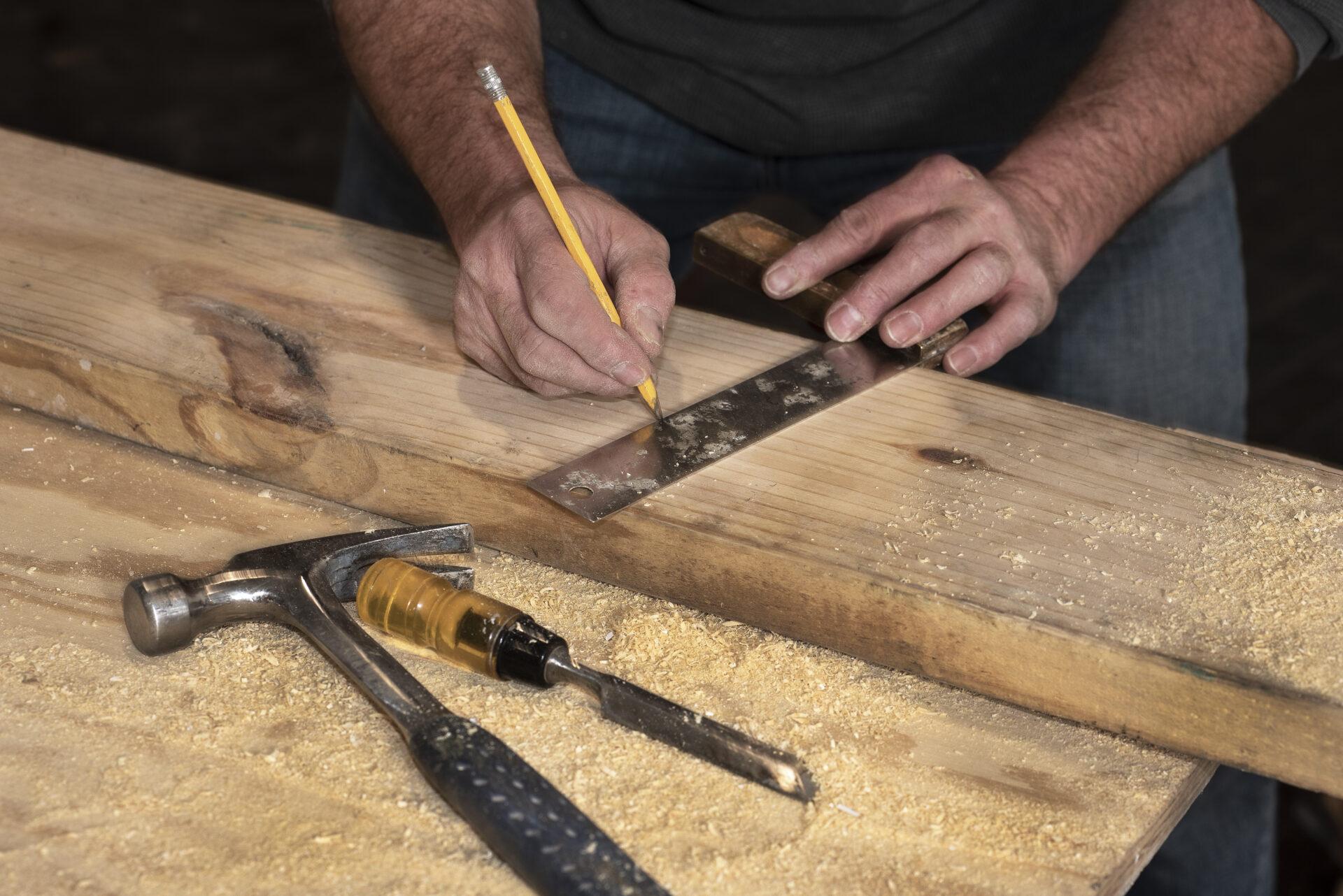 Carpenter marking measurements during renovation of fixer-upper